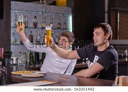 Two young men raising their beers in a toast cheering as they celebrate with friends in the pub - stock photo