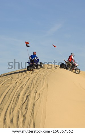 Two young men riding quad bikes on sand dune in desert - stock photo