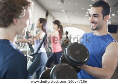 Two young men smiling and lifting weights in gym - stock photo
