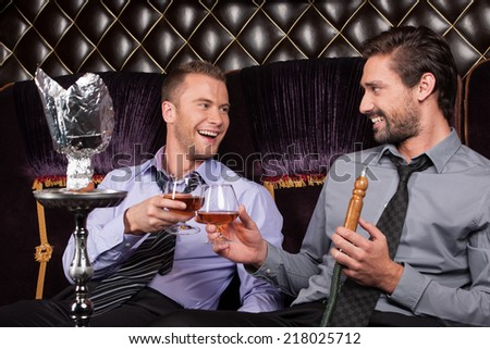 two young men smoke from shisha pipe. business friends drinking and smiling in restaurant