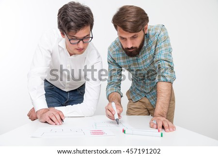 Two young men working together at table. One of them is drawing while other looking. Markers in hand. Concept of development