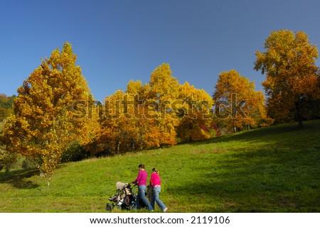 Two young mothers walk with their pushchairs past trees bright with autumn colours. - stock photo