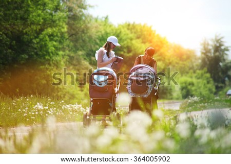 Two young mothers walking with prams - stock photo