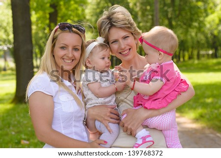 Two young mothers with baby girls in park - stock photo