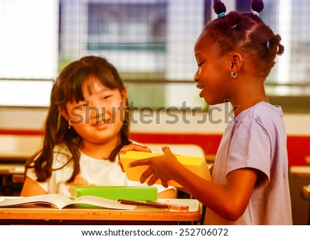 Two young multiracial african asian girls smiling at classroom desk. - stock photo