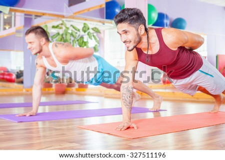 Two young multiracial men doing pushups indoor at fitness class. By doing the exercises every day, you have successfully pump up muscles strong and beautiful