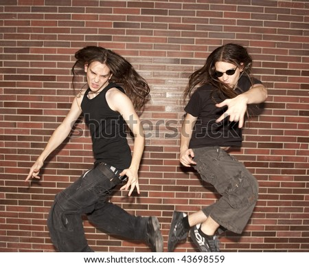 Two young musician jumping against brick wall - stock photo