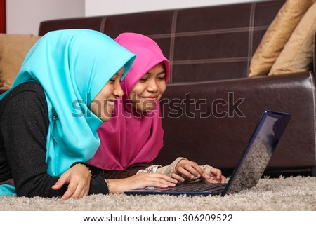 two young muslim women using laptop while lying on floor at home - stock photo