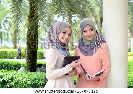 Two young Muslim women with notebook while relaxing in the park  - stock photo