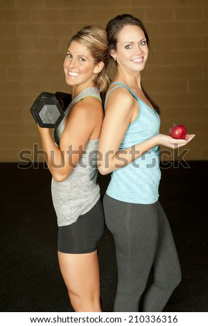 Two young nutritionists posing in a gym - one with an apple and one with weights. - stock photo