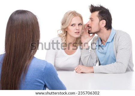 Two young people are gossip about their friend on white studio background. - stock photo