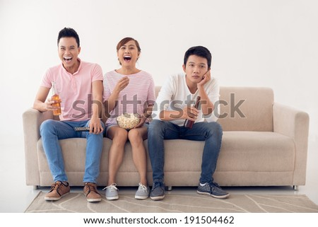 Two young people laughing when watching television, while their friend is sad