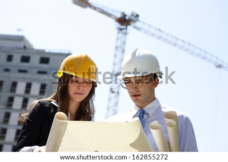 Two young people looking and discussing the blueprints. - stock photo