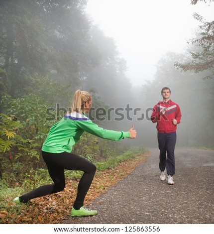two young people making fun while jogging