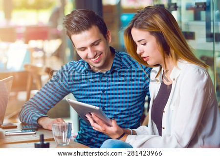 Two young people, man and woman, looking at a tablet - stock photo