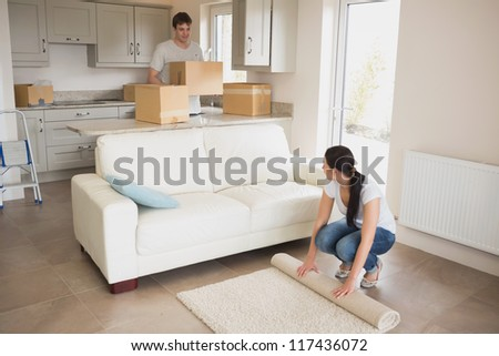 Two young people moving into their house and furnishing the living room - stock photo