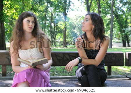 Park one teenager smoking cigarette annoys another girl stock photo