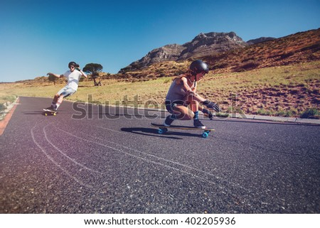 Two young people practicing long board riding outdoors on rural road. Man and woman longboarding on a summer day. - stock photo