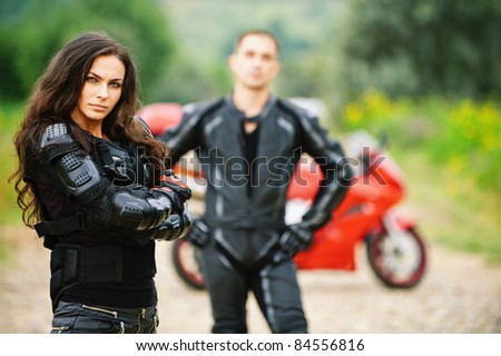 Two young people: pretty brunette woman and handsome man standing against red motorbike.