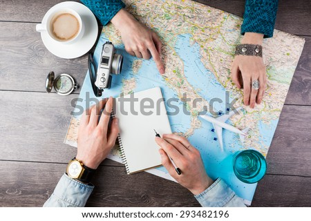Two young people together planning trip to Europe. Top view. empty white space in notebook where you can place your text or advertisement.  Romantic travel - stock photo