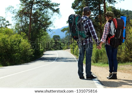 Two young people tourists hitchhiking along a road. - stock photo