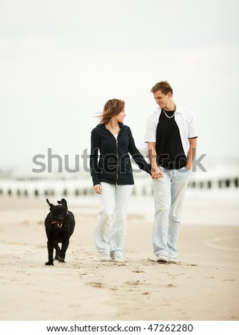 two young people walking on the beach holding tight with dog