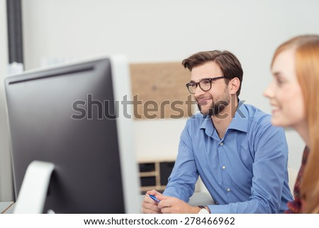 Two young people working in the office with a view past the face of a smiling woman to a businessman working at his desktop computer - stock photo