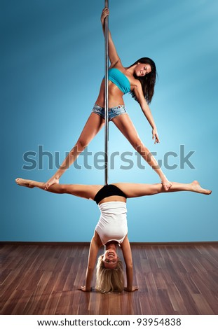Two young pole dance women. - stock photo