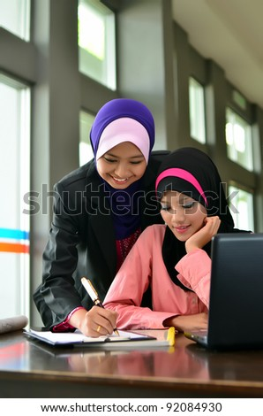 Two young pretty Asian muslim business woman in head scarf  study for sucess