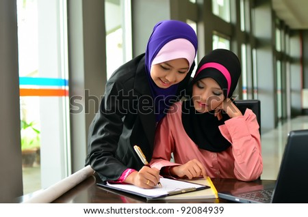 Two young pretty Asian muslim business woman study together