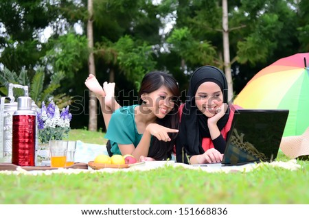 Two young pretty Asian muslim college girl with book and laptop.  - stock photo