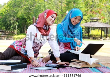 Two young pretty Asian Muslim Student in head scarf with book laptop - stock photo