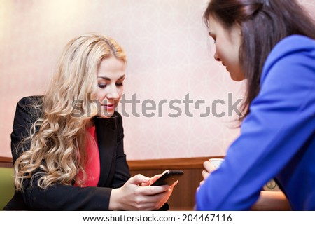 Two young pretty caucasian girls with long hair chatting and having fun at a cafe and looking at smartphone - stock photo
