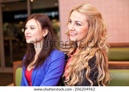 Two young pretty caucasian girls with long hair in restaurant looking at something exciting - stock photo