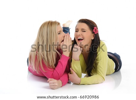 Two young pretty girls gossiping and enjoying conversation. isolated on white background - stock photo