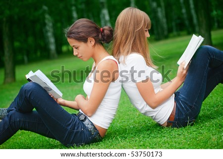 Two young pretty girls reading books - stock photo