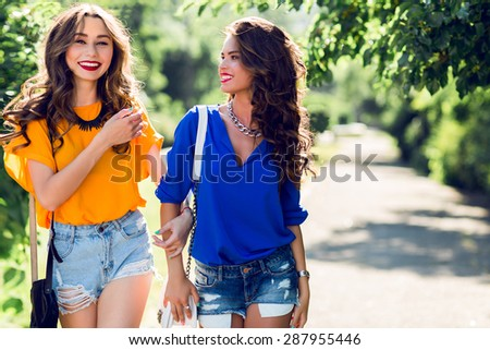 Two young pretty girls walking in sunny summer park.  Girlfriends enjoying their time together and celebrate  holidays.  - stock photo