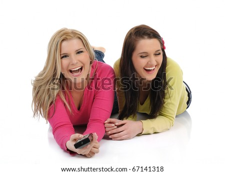 two young pretty woman friends watching television and switching channels on remote control - stock photo