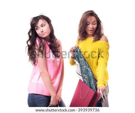two young pretty woman standing isolated on white background paper shopping bags from the store. dissatisfied with the girl because a friend bought her dress - stock photo