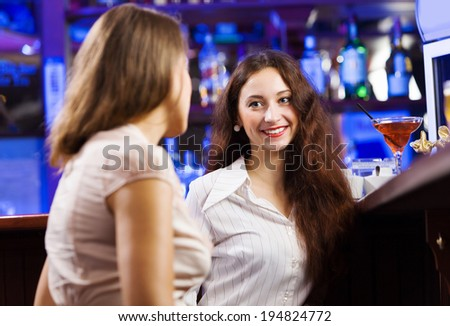 Two young pretty women at bar and drinking cocktails