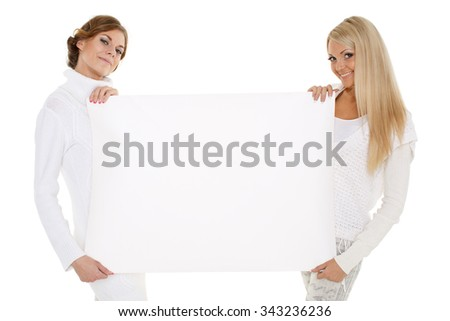 Two young pretty women in winter clothes with empty board for the text on a white background. - stock photo