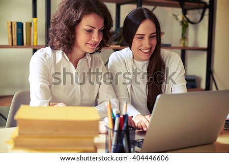 Two young pretty women sitting at the table and working at a laptop, bookshelves on a background