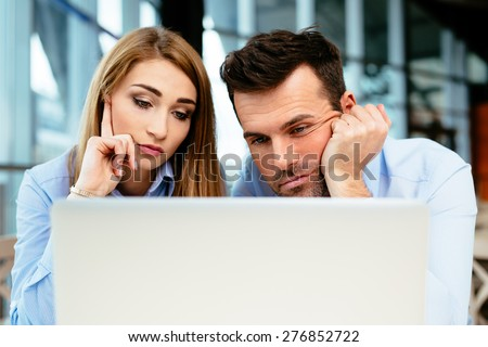 Two young professionals unhappy to see some data on the screen - stock photo