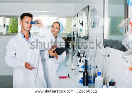 Two young researchers in white coat checking wine acidity and sugar saturation in chemical laboratory