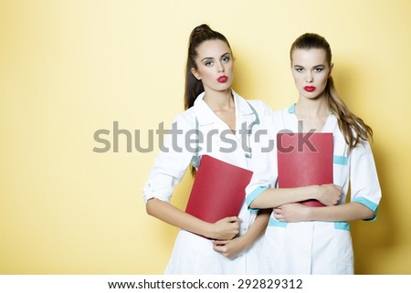 Two young serious sexy attractive doctor and nurse in white medical uniform with stethoscope on neck holding purple file of clinical record standing on yellow background copyspace, horizontal picture - stock photo