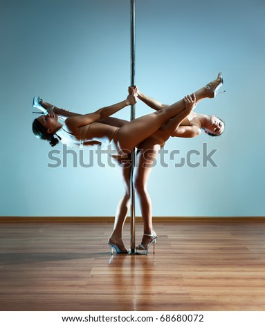 Two young sexy pole dance women. - stock photo