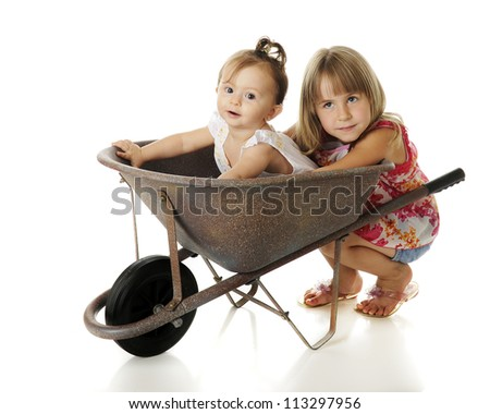Two young sisters -- an adorable baby in an old wheelbarrow, her sister squatting on the ground behind her.  On a white background. - stock photo
