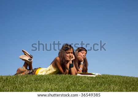 two young sisters at the park reading a book - stock photo