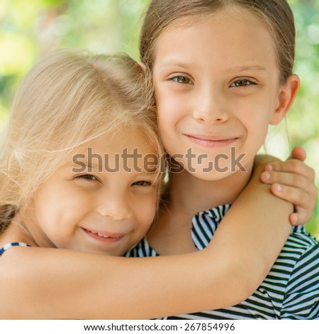 Two young sisters hugging, in summer city park. - stock photo
