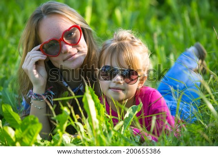 Two young sisters lying in the grass, sun-glasses, looking into the camera. - stock photo